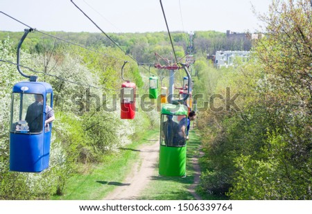Lots of colourful cabins on rope in the city park. Panorama of cablecars - electric cabin transport. #1506339764