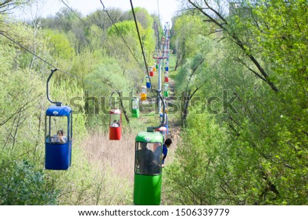 Lots of colourful cabins on rope in the city park. Panorama of cablecars - electric cabin transport. #1506339779