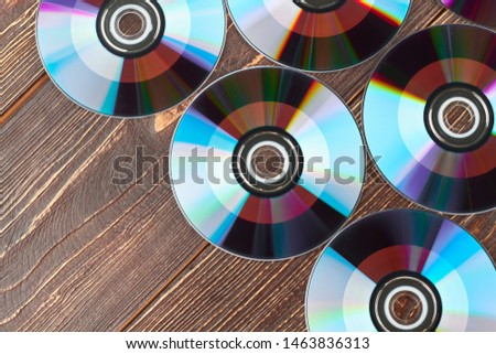 Lots of compact discs and copy space. Colorful dvd discs on brown wooden background close up.