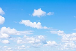 Lots of cumulus clouds far on horizon on blue daylight sky as natural background