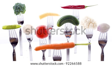 Lots of different fresh vegetables on forks isolated on white background