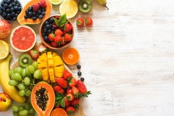 Lots of different fruits, strawberries, blueberries, mango, orange, grapefruit, banana, apple, grapes, kiwis on the white background, copy space for text, selective focus