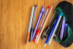 Lots of different pen and pencils spreading through black pencil holder on wooden table.Study for exams and education concept. Pile of pencils of different colors.copy space.work in distance education