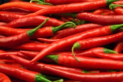 Lots of fresh large red spicy chilly peppers shot from overhead at outdoors market