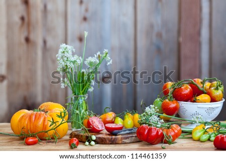 Lots of fresh tomatoes and garlic flowers with wooden background