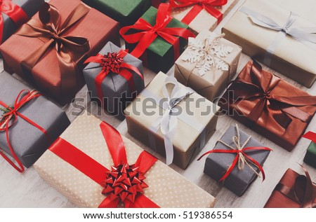 Lots of Gift boxes on wood background. Presents in craft and colored paper decorated with red ribbon bows and snowflakes. Christmas and other holidays concept. #519386554