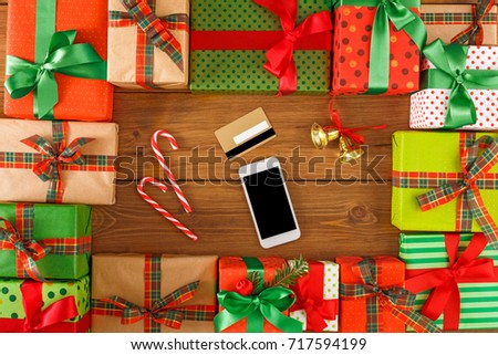 Lots of Gift boxes, xmas bells, xmas candy on wood background top view, flat lay. Presents in craft and colored paper decorated with red and green ribbon bows. Mobile phone, card. #717594199
