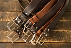 Lots of handmade men's leather belts on a wooden background. Classic men's leather belts in brown and cognac color. Handmade leather belts. Leather craft