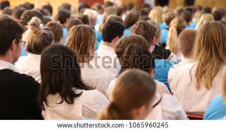 Lots of heads from behind. High Middle School assembly. mixed shot of girls boys, male female in various uniforms  listening attentively facing front of the hall. Educational speech. hair. audience