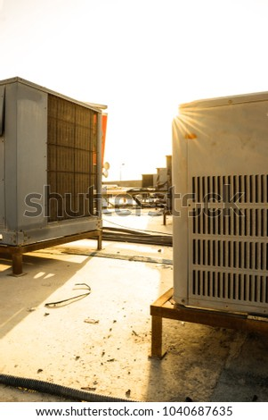 lots of heavy duty units of central air conditioning system kept on the roof top of a building and sunburst in the background    #1040687635