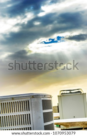 lots of heavy duty units of central air conditioning system kept on the roof top of a building and sunshine in the background    #1070953079