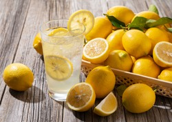Lots of lemons and lemon sours in a basket on a wooden background