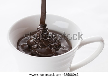 lots of melted chocolate falling in white cup