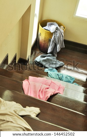 Lots of messy clothes on a cloth basket and stair wooden floor
