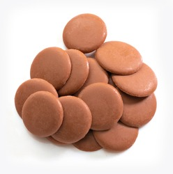 Lots of milk chocolate disks on white background. Isolated. View from above