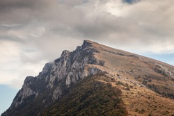Lots of mountain hikers climbing to Trem peak on Dry mountain (Suva planina), autumn colors and dramatic sky above the summit