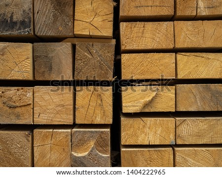Lots of planks stacked on top of each other in the warehouse. Lumber for further use in construction. Texture, background