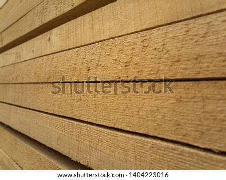 Lots of planks stacked on top of each other in the warehouse. Lumber for further use in construction. Pile of sawn boards