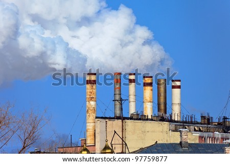 Lots of smoking chimneys other blue sky background