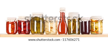 Lots of various homemade preserves on a wooden shelf - stock photo