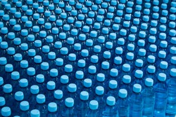 Lots of water bottles. Bottles with blue caps. Simple means perfect. Merchandise supplied to supermarkets.