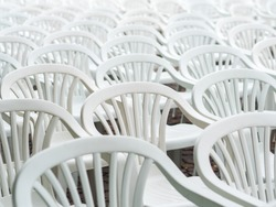 Lots of white plastic chairs. Abstract background.Selective focus. Image of a bunch of white plastic deck chairs.