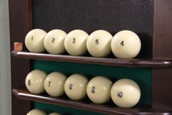 Lots white balls on the shelf-stand for billiard balls in one row for playing Russian Billiards. vintage cabin Russian sport and fun for guests