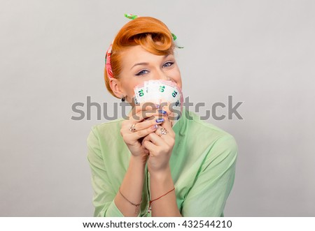 Lottery win. Closeup red head beautiful young woman pretty happy smiling pinup girl green button shirt holding euro money and smelling aroma smiling looking at you camera, retro vintage 50's hairstyle