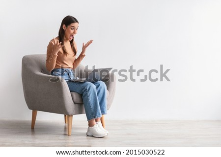 Lottery win, good luck, success, amazing online sale. Emotional young woman sitting in armchair with laptop, looking at screen, shouting in excitement, winning huge casino bet, copy space