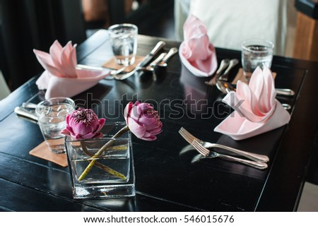 Lotus in glass vase on dinnertable. select focus at flower lily on wooden table with set of napkin prepare for dinner at restaurant.