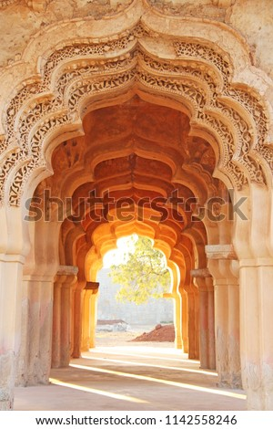 Lotus Mahal Temple in Hampi, Karnataka, India. Beautiful carved stone arch and sunset. A popular tourist route from the GOA state. Beautiful hindu temple. #1142558246