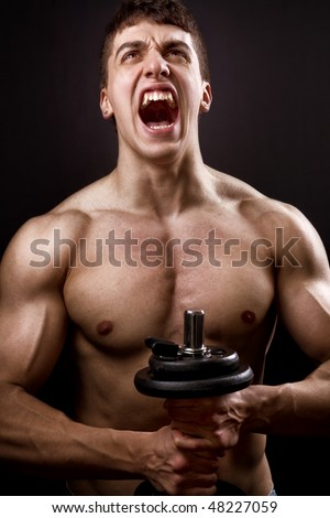 Loud scream of powerful muscular bodybuilder over black