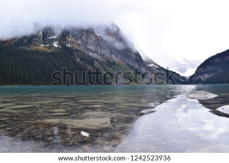 Louise Lake. Pic take close to the water. With mountain reflection. Grey cloud and white sky.