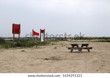 Louisiana wildlife and nature background. Beach area view at the Grand Isle State Park, Louisiana, South USA. Red flag marks dangerous swimming conditions.