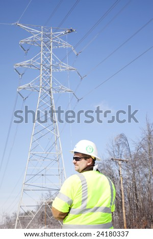 LOUISVILLE - 31 JANUARY: Pike Electric Supervisor, Tom Wallace, watches the work area as a worker repairs the top of a high tension line tower after ice damage from January 2009 storm.
