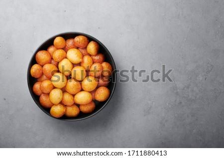 Loukoumades or luqaimat or lokma in black bowl on grey concrete background. Loukoumades is eastern cuisine donunts popular during Ramazan. Popular Ramadan Food. Iftar and Suhur sweets