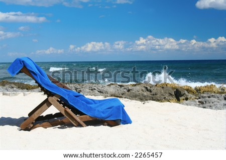 Lounge chair and beach towel on a beautiful deserted  beach.