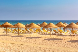 Lounge chairs and parasols in a row on Albufeira beach, Algarve, Portugal