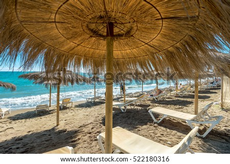 Shutterstock Lounge chairs and straw umbrellas at the beach in Malaga. Costa del Sol, Andalusia, Spain