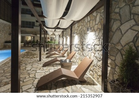 Lounge chairs by the swimming pool at night