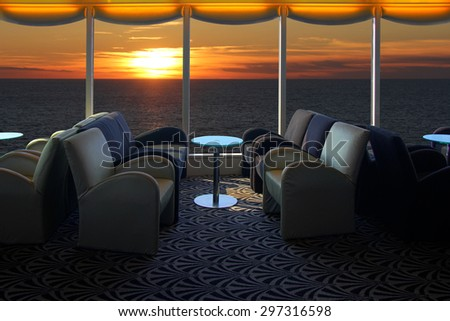 Lounge on a cruise ship, with tables and armchair in the sunset at sea