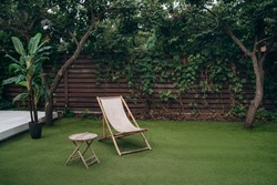 Lounge zone. Wooden lounge chair and table on lawn grass in a garden. Rest relaxation place. rest concept