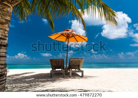 Loungers and umbrella on tropical beach in Maldives Island, Indian Ocean. Luxury summer travel vacation holiday background concept. #479872270