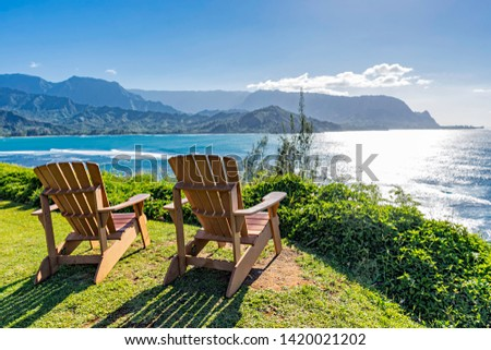 lounging chairs overlooking Hanalei Bay and the Na Pali coast Princeville Kauai Hawaii USA in the late afternoon sun Stock photo ©
