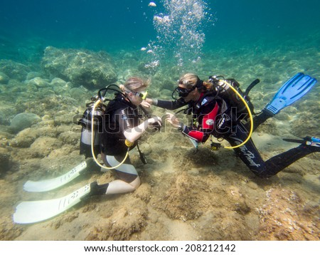LOUTRA,GREECE - JULY 26 2014 : Female Scuba Divers take part in a traing dive.More women are taking up the adventurous sport  of scuba diving .There are dive schools in most countries around the world #208212142