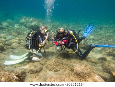 LOUTRA,GREECE - JULY 26 2014 : Female Scuba Divers take part in a traing dive.More women are taking up the adventurous sport  of scuba diving .There are dive schools in most countries around the world #208212154