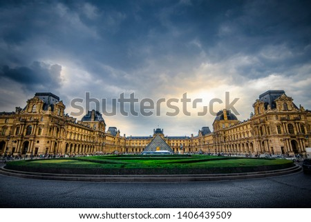 LOUVRE MUSEUM, PARIS, FRANCE - Wide angle shot of Louvre Palace, including famous glass pyramid entrance to art museum, with dramatic clouds in the sky. Iconic, historic landmark/destination #1406439509
