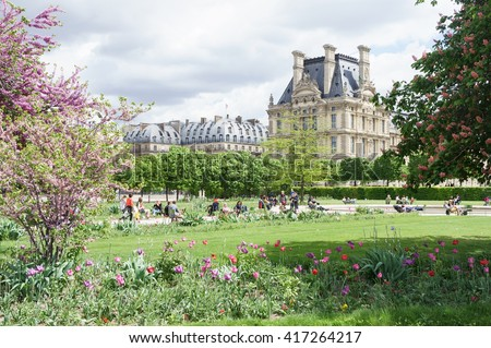 Louvre palace and Tuileries garden spring day view in Paris, France. Spring gardens in front of Louvre palace in Paris. Louvre palace view at sunny day in Paris, France. Paris sights. Paris scene.