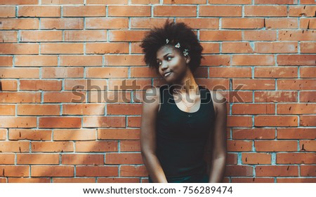 Lovable black young female in front of brick pattern background on summer day looking aside; portrait of calm dainty African American teenage girl next to brick wall with copy space place for advert