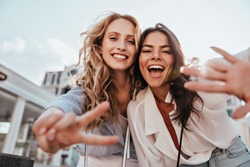 Lovable caucasian girls expressing positive emotions to camera. Outdoor photo of refined sisters posing on sky background.